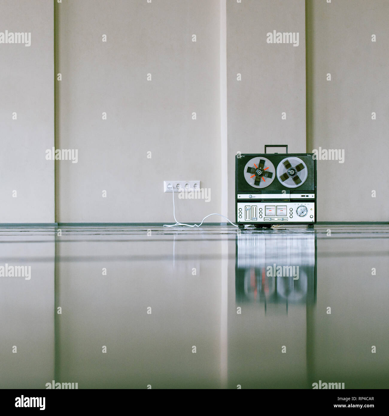 vintage analog magnet tape recorder standing on the floor near wall. Stock Photo