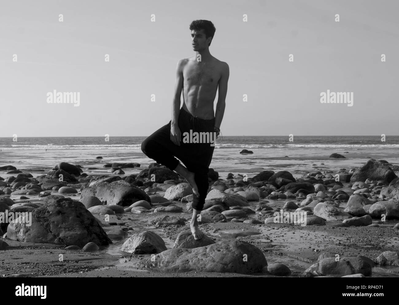 Black and white portrait of a young man in yoga pants and shirtless in the beach. Relaxing tree pose - Stock Image