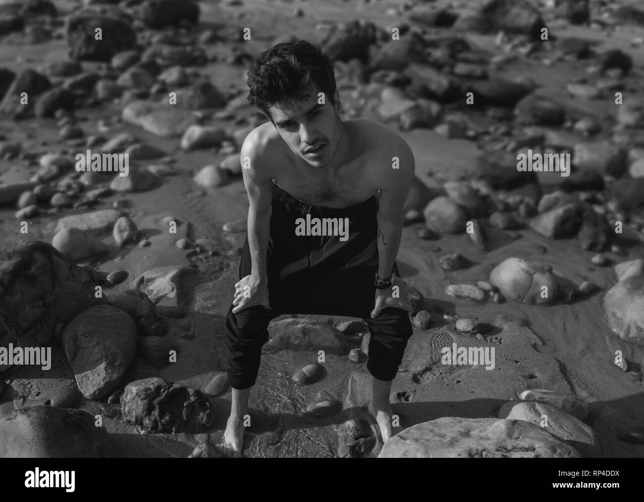 Black and white portrait of a young man in yoga pants and shirtless in the beach. looking at the camera - Stock Image