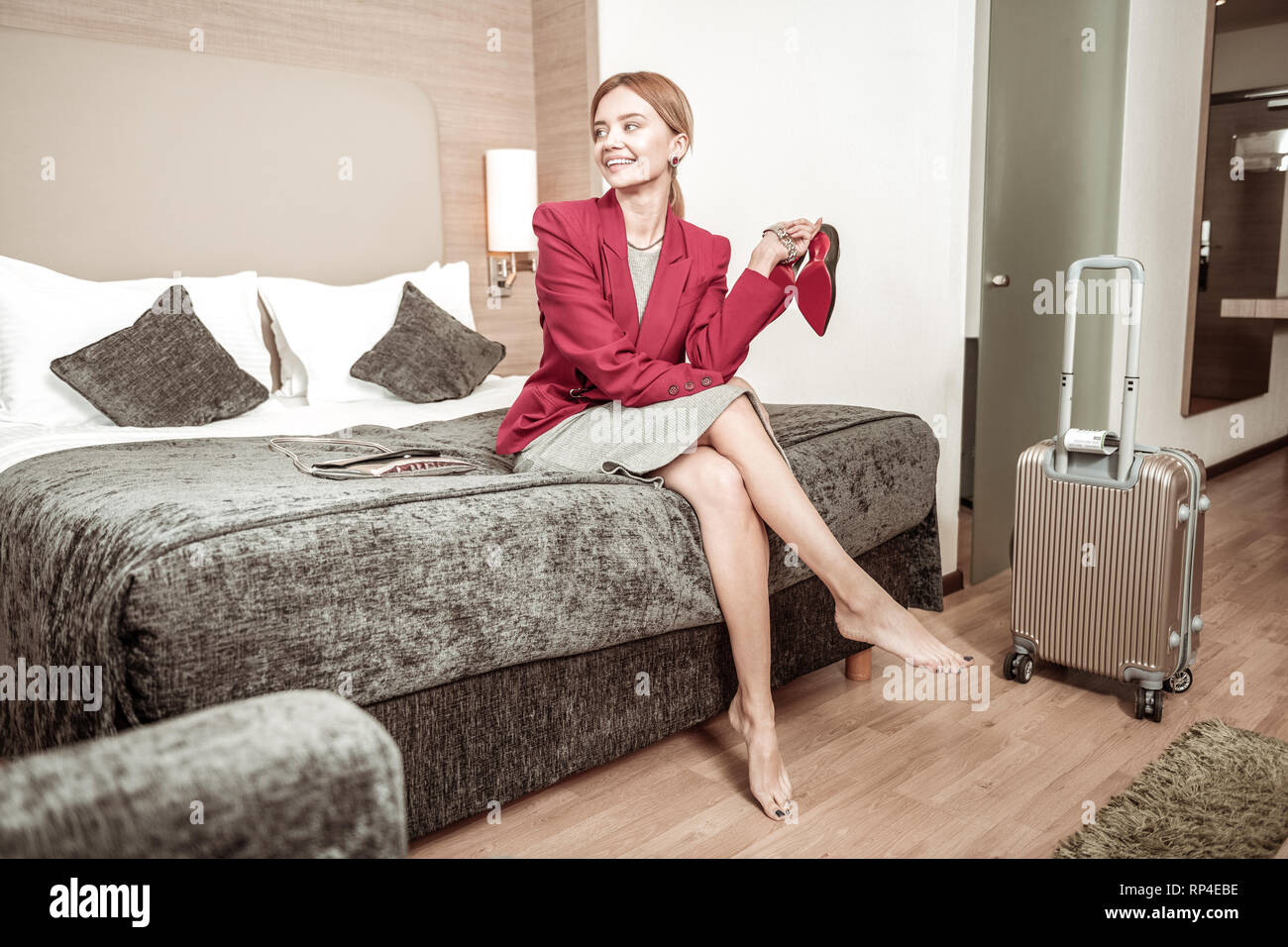 Blonde-haired businesswoman sitting on big comfy bed in hotel - Stock Image