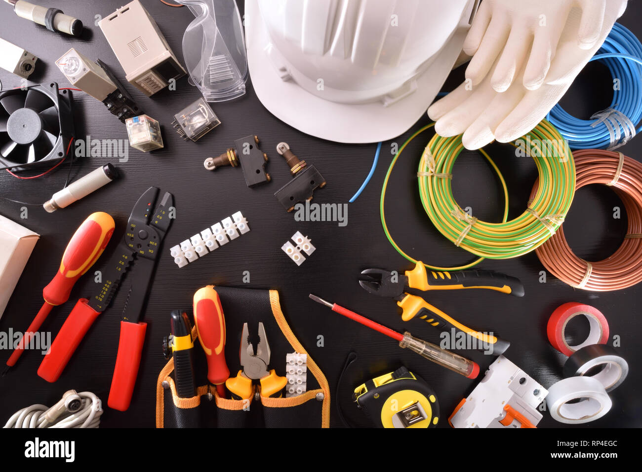 Black table with industrial equipment and tools for installation, repair and maintenance of electrical panels and electrical machinery. Horizontal com - Stock Image