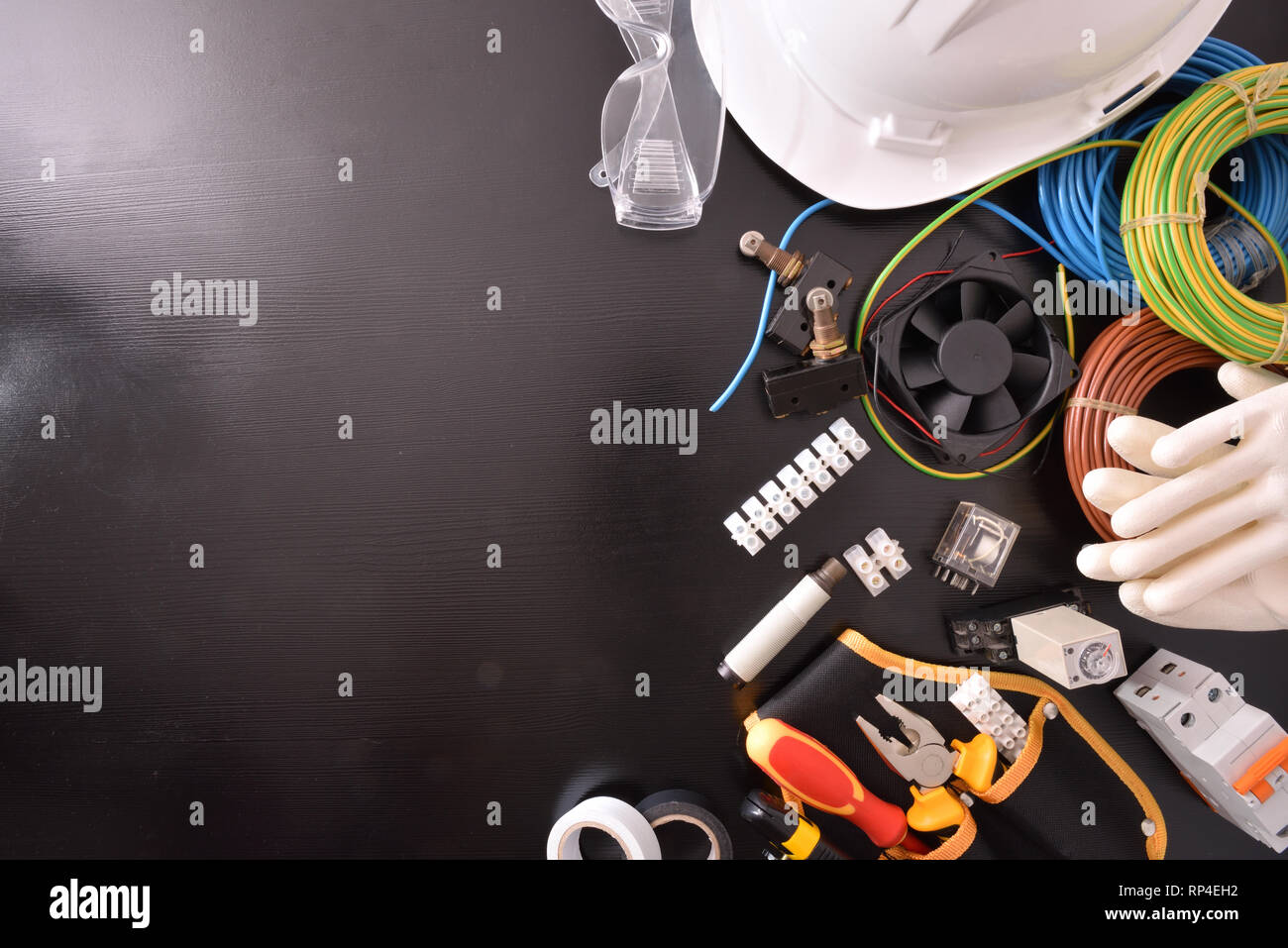 Black table with industrial equipment and tools for installation, repair and maintenance of electrical panels and electrical machinery space on the le - Stock Image
