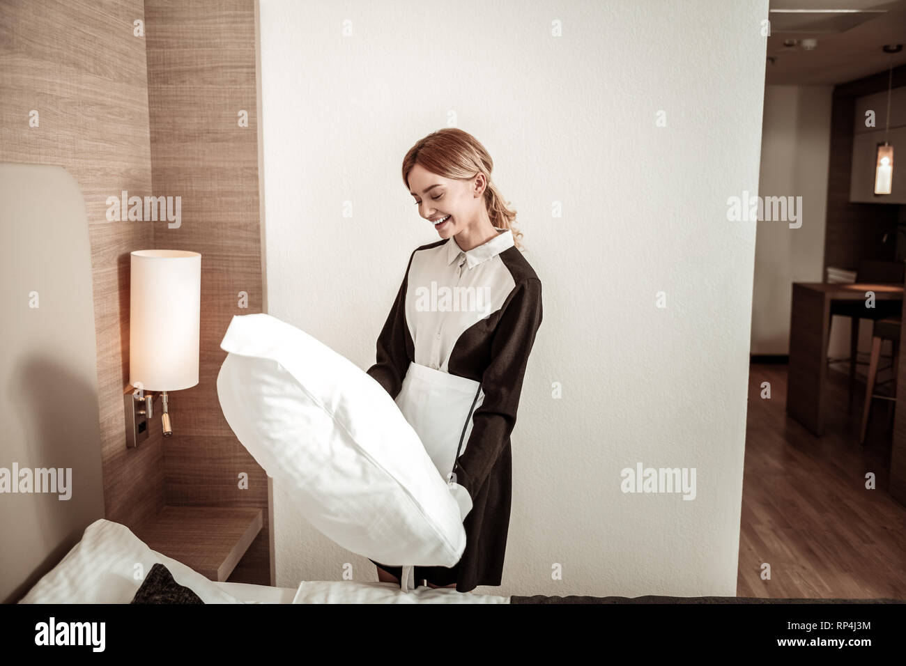 Cheerful hotel maid holding big comfy white pillow - Stock Image