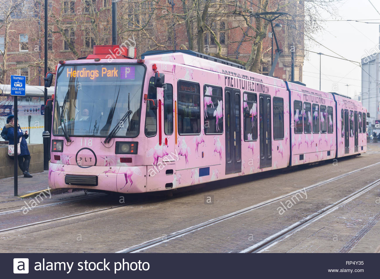 A pink Supertram advertising Pretty Little Thing at the tram stop in Cathedral Square in Sheffield, South Yorkshire, England, UK - Stock Image