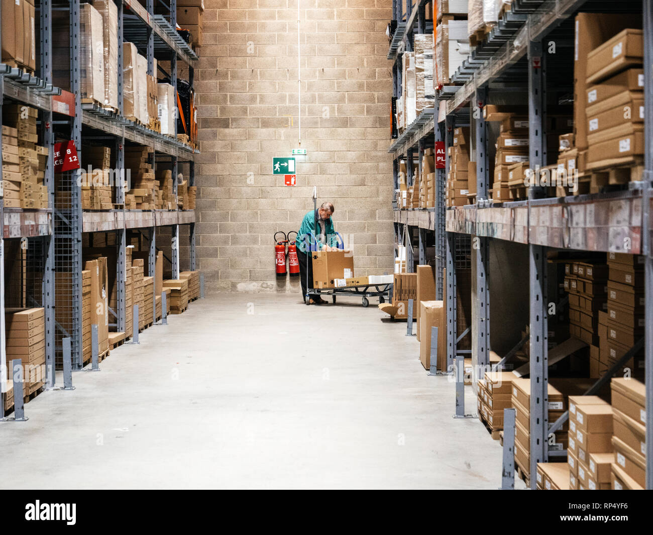 STRASBOURG FRANCE - SEP 3 2017: Perspective view of old senior man in furniture warehouse among shelves with carton boxes on trolley cart IKEA furniture shopping - Stock Image