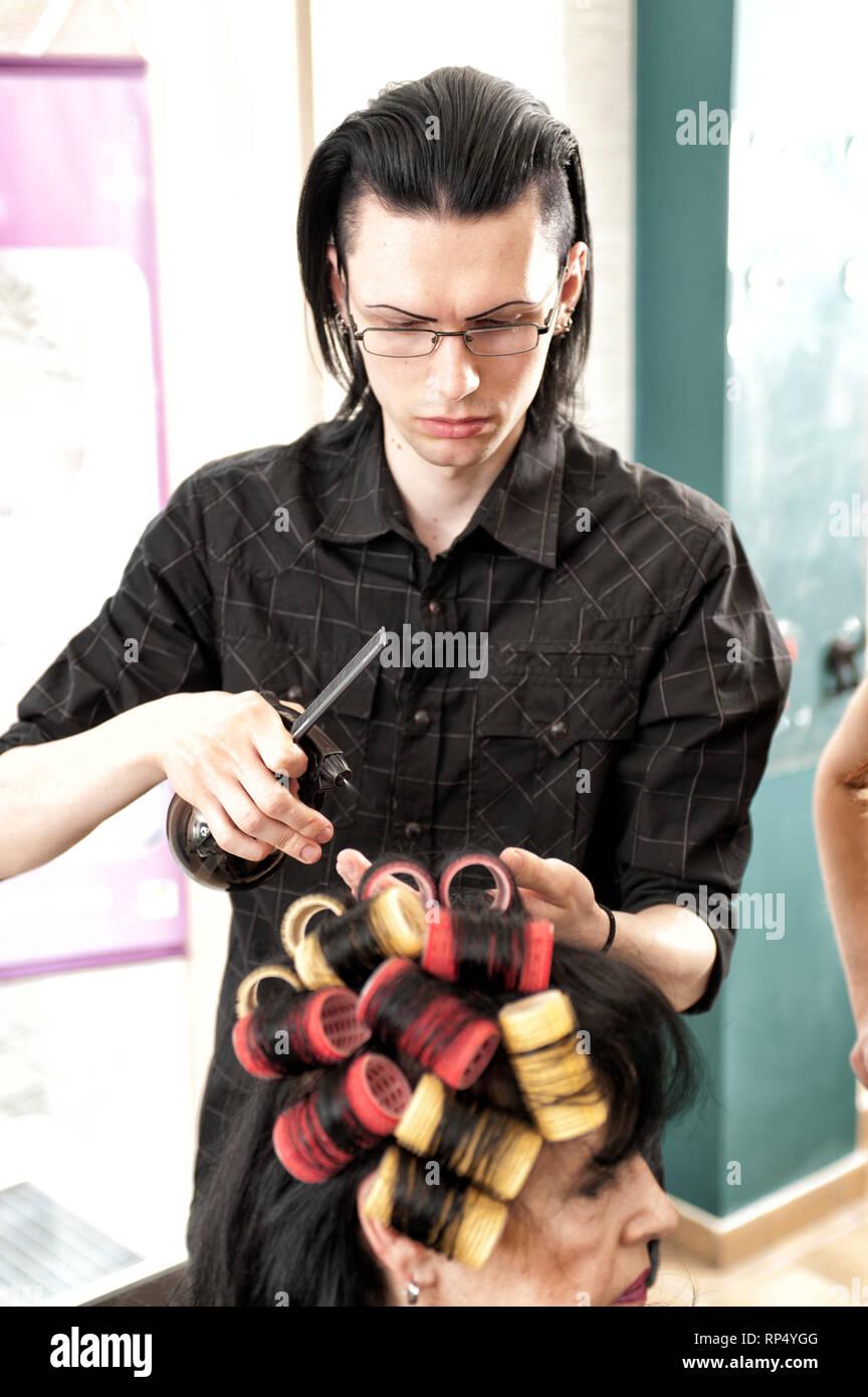 Ein Auszubildender im Friseurhandwerk setzt bei einer Kundin Lockenwickler ins Haar. Beide sind schwarzhaarig, die Lockenwickler rot und gelb. [(c) Di - Stock Image