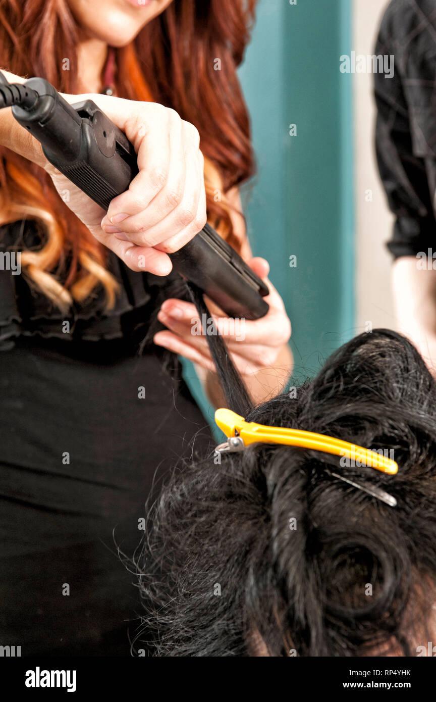 Eine junge, rothaarige Friseurmeisterin demonstriert an einer Kunden ihrem jungen maennlichen Auszubildenden wie Haare geglaettet werden. [(c) Dirk A. - Stock Image
