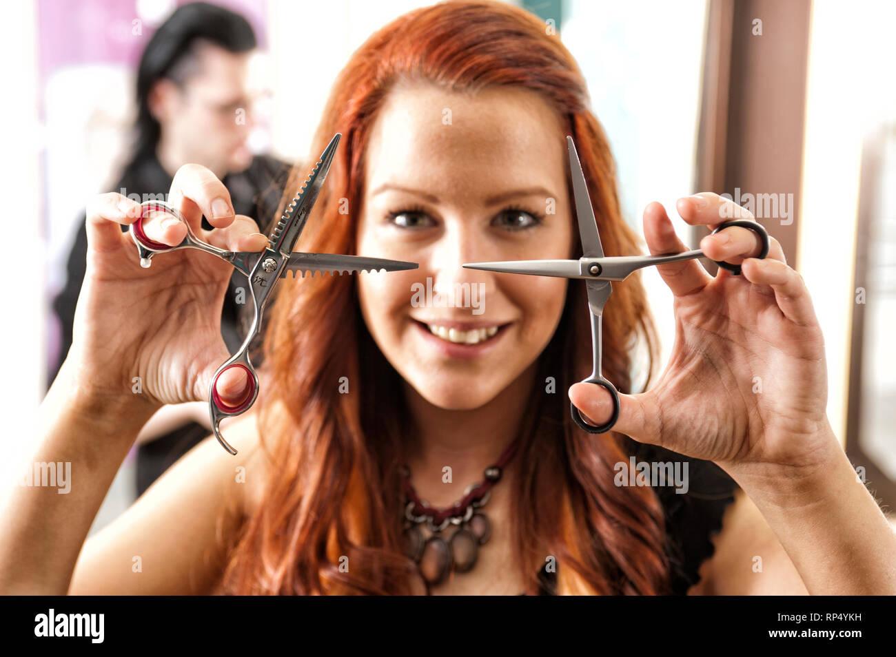 Junge rothaarige Friseurmeisterin posiert mit Scheren vor sich fuer ein Foto. Im Hintergrund arbeitet ihr schwarz haariger Lehrling [(c) Dirk A. Fried - Stock Image