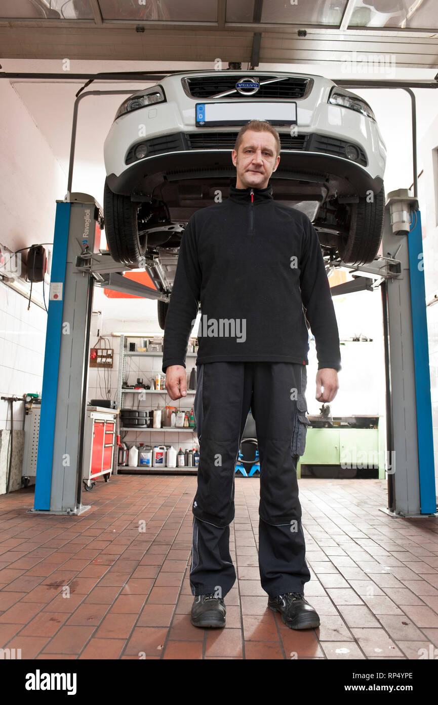 Selbstaendiger KFZ Meister steht vor einem Auto das ueber ihm auf der Hebebuehne schwebt, Er steht frontal und die Arme haengen neben seinem Koerper,  - Stock Image