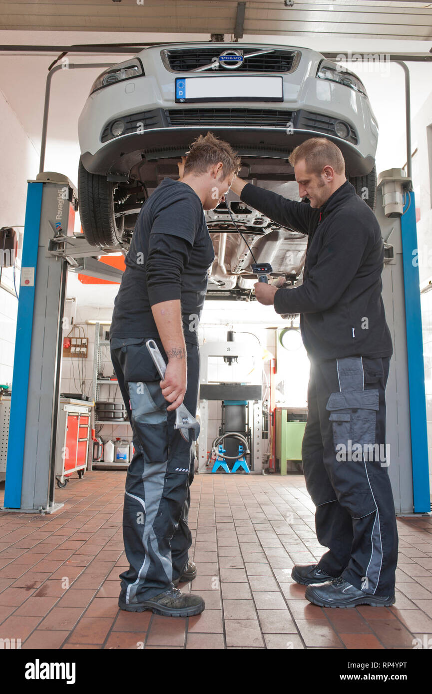 KFZ Teckniker Meister erklaert seinem Lehrling zum KFZ Mechatroniker wie eine Endoskop-Kamera funktioniert. In einer kleinen Werkstatt. [(c) Dirk A. F Stock Photo
