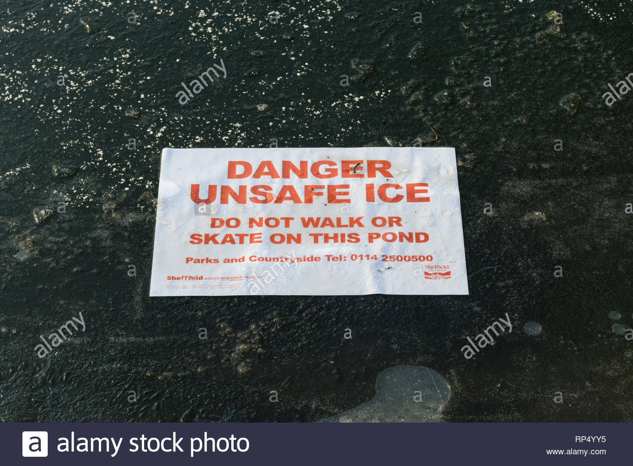 Notice placed on the frozen ice on the lake  in Weston Park, Sheffield, South Yorkshire warning Danger Unsafe Ice, Do not walk or skate - Stock Image