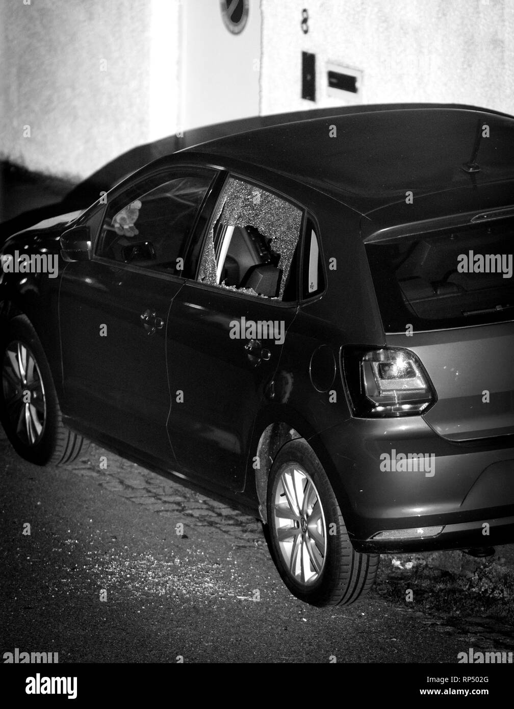 PARIS, FRANCE SEP 26, 2018: Detail of night scene of elevated view of a new red car with the broken glass window shattered glass on asphalt - robbery, break-in, burglary, embezzlement felony in calm neighborhood - black and white - Stock Image