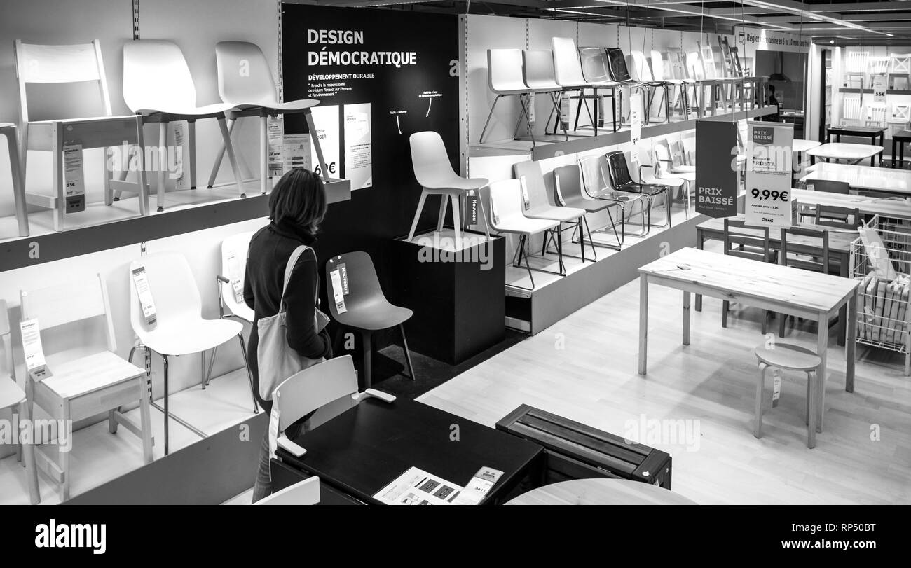 PARIS, FRANCE - SEP 9, 2017: View from above of French adult woman shopping for chairs furniture in the IKEA shopping furniture mall center black and white - Stock Image