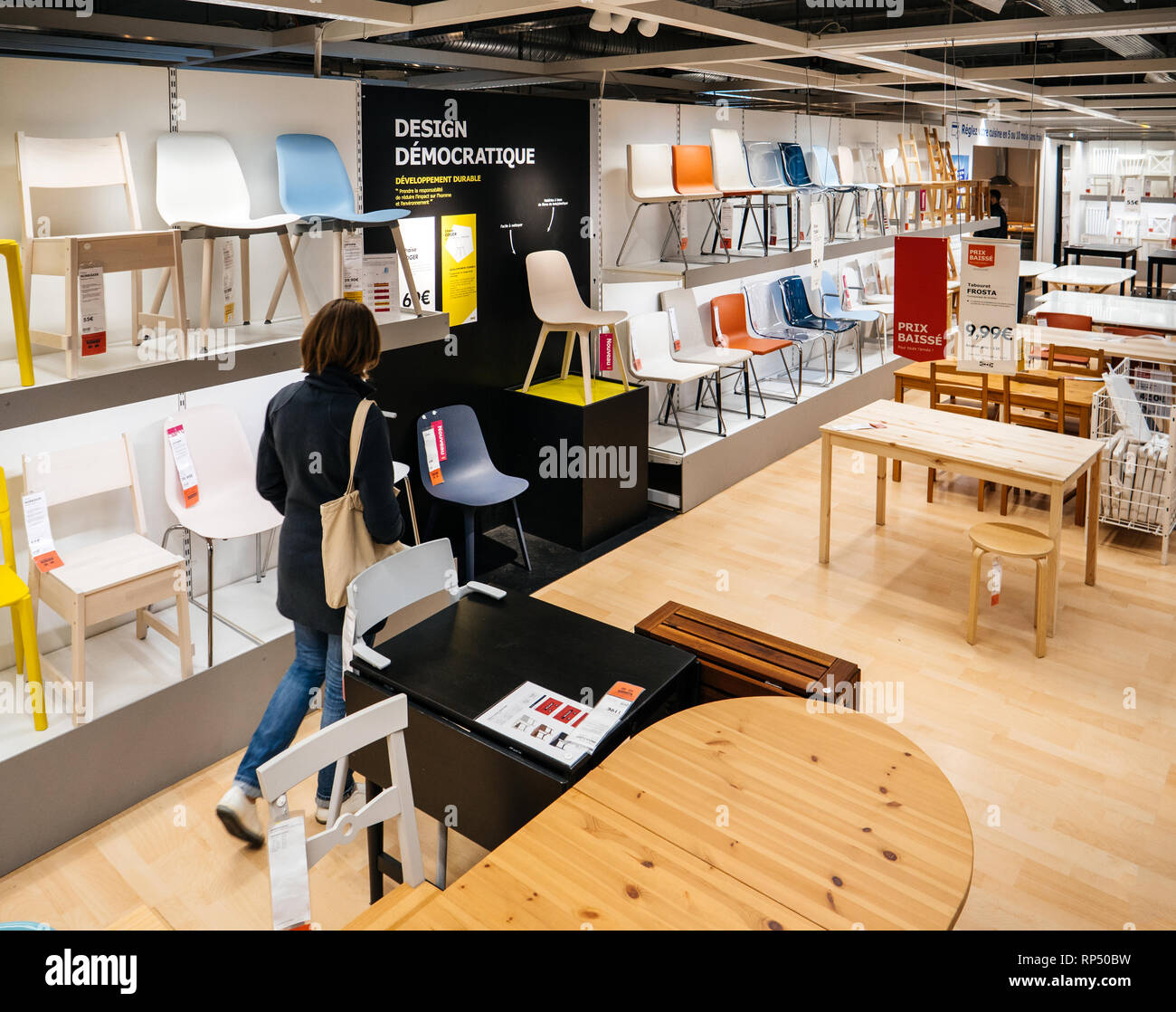 PARIS, FRANCE - SEP 9, 2017: View from above of French adult woman shopping for chairs furniture in the IKEA shopping furniture mall center - Stock Image