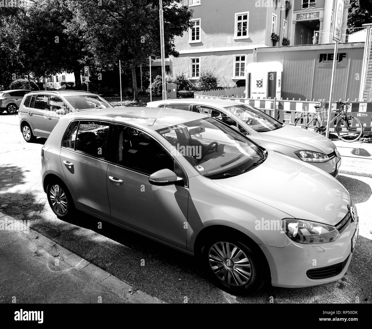 KEHL, GERMANY - SEP 1, 2017: Side elevated view of fleet of Volkswagen Golf cars parked near construction site in German city black and white - Stock Image