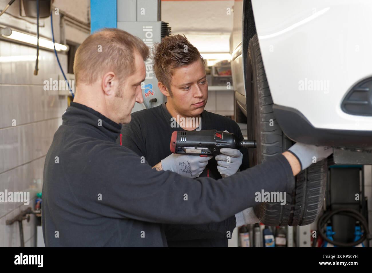 KFZ Teckniker Meister erklaert seinem Lehrling zum KFZ Mechatroniker. In einer kleinen Werkstatt [(c) Dirk A. Friedrich Stock Photo