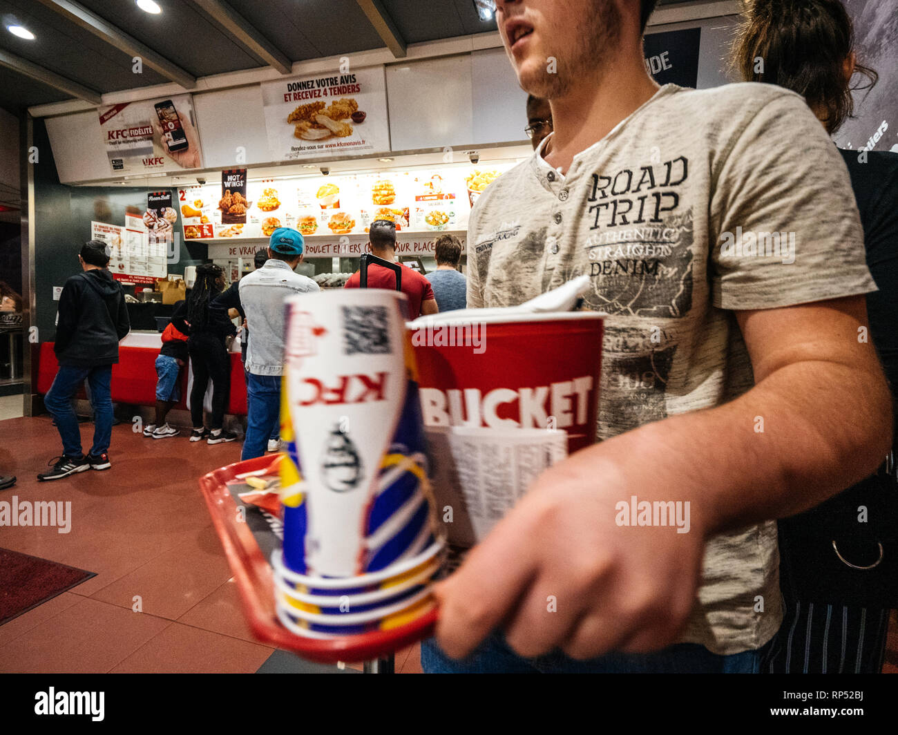 PARIS, FRANCE - OCT 13, 2018: man with lots of fast-food inside KFC Kentucky Fried Chicken restaurant Stock Photo