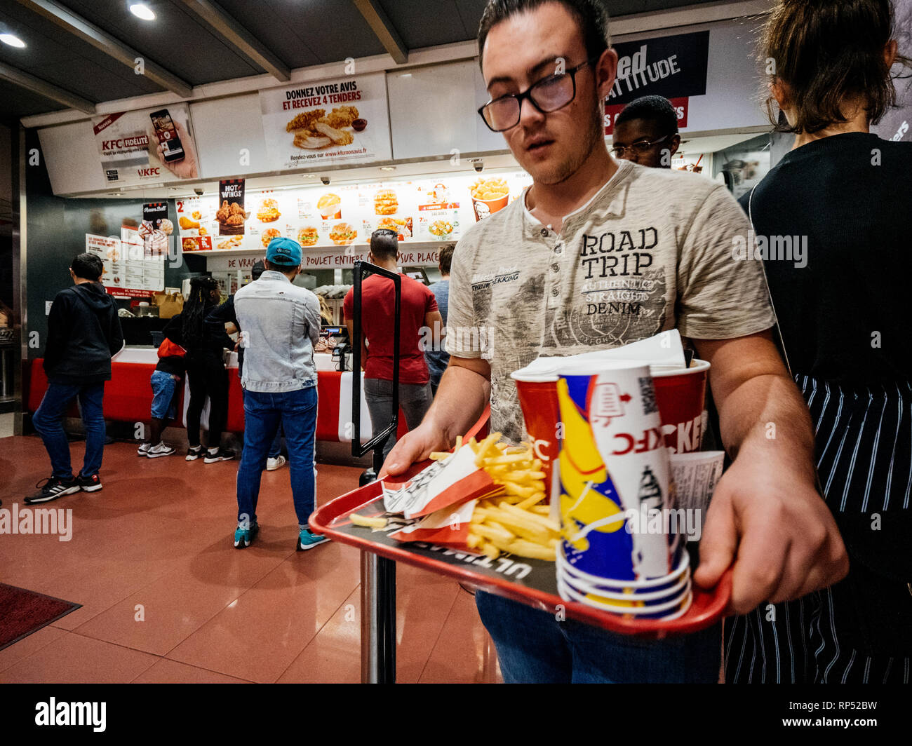 PARIS, FRANCE - OCT 13, 2018: Young man with lots of fast-food inside KFC Kentucky Fried Chicken restaurant Stock Photo