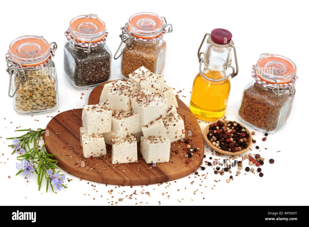 Vegan health food with tofu bean curd dusted with alfalfa seed & ground pepper, with flax, hemp and chia seeds, olive oil, rosemary herb & peppercorns. - Stock Image