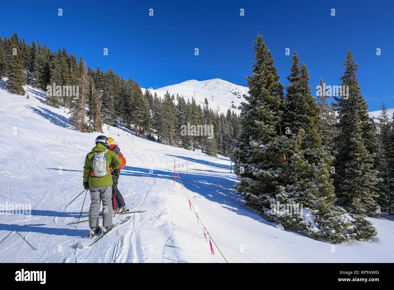 Two Skiers walking along the snow of the Colorado Rocky Mountains at Copper Mountain Ski Resort in winter - Stock Image