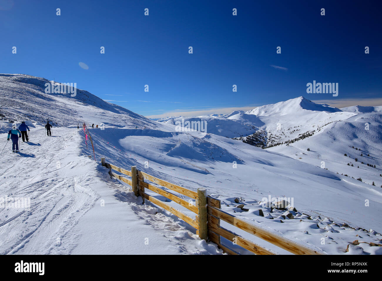 Skiers walking along the top of the mountain of the Colorado Rocky Mountains at Copper Mountain Ski Resort in winter - Stock Image