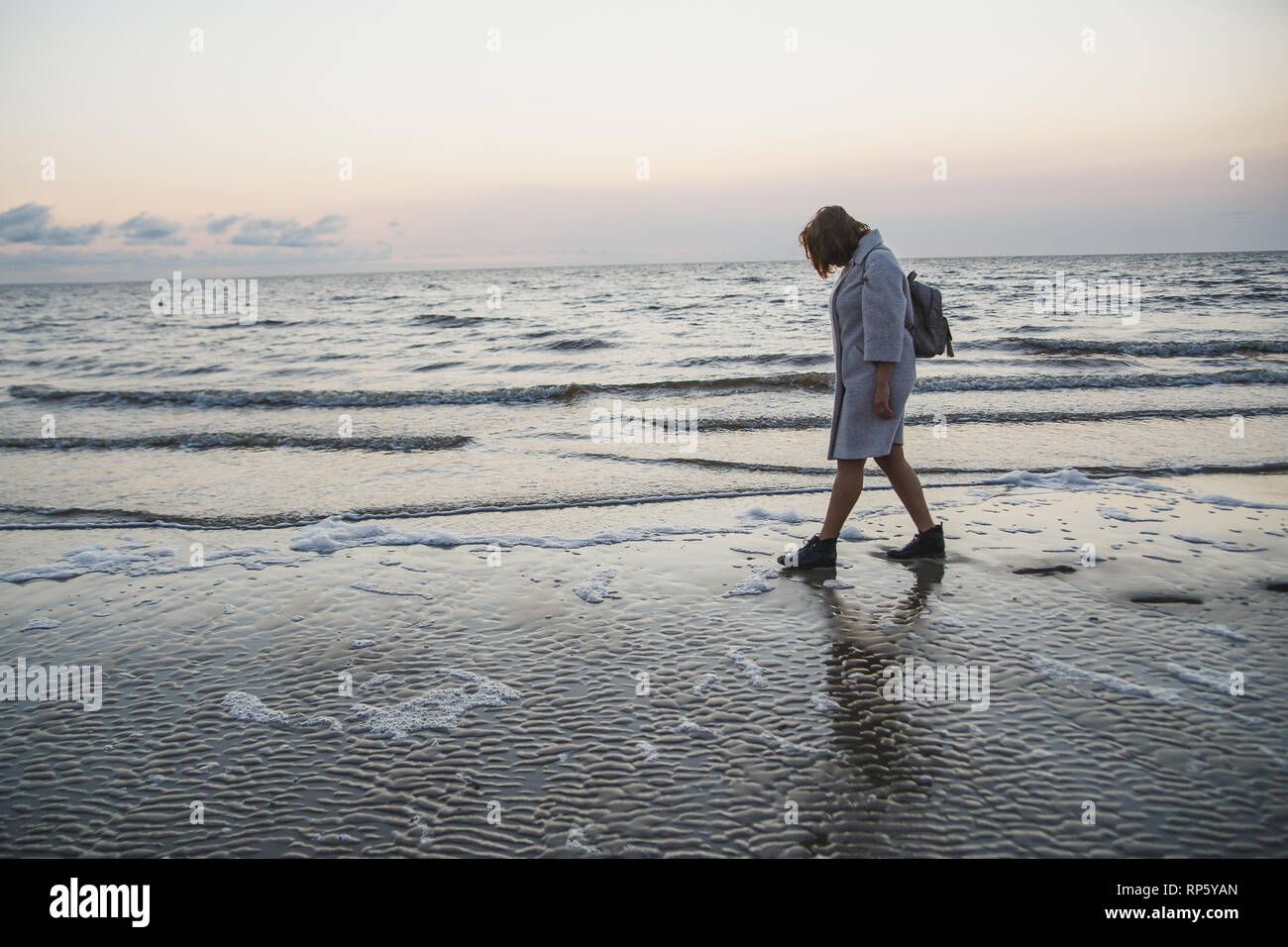 Alone girl in coat and leather boots walking along seashore.