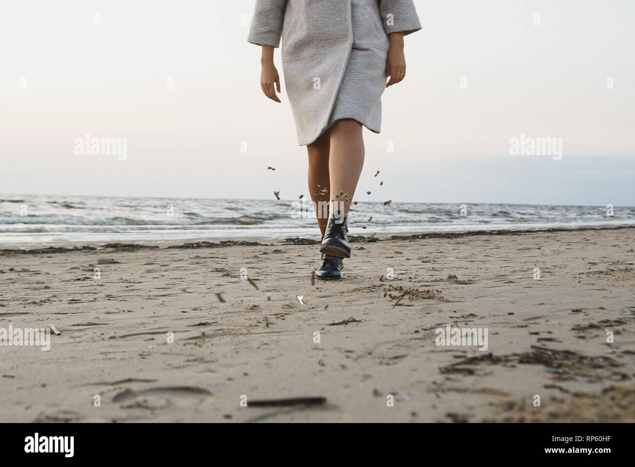 Carefree woman in black leather boots kick sand on beach. Flying wet sand. Concept footwear protection, water and dust resistance. - Stock Image
