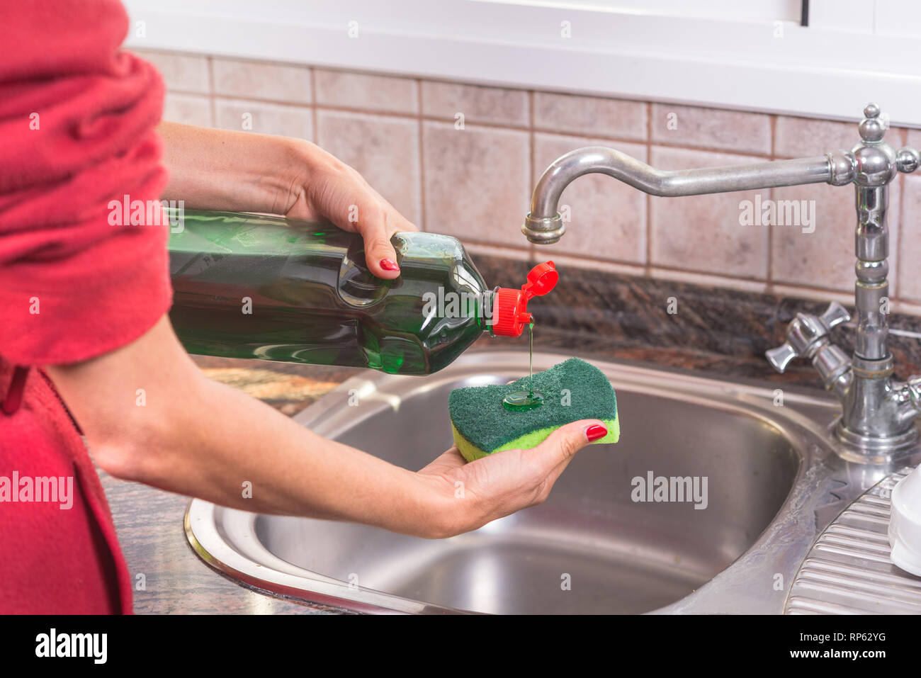 woman with red manicure putting detergent in the scourer, to wash the dishes . - Stock Image
