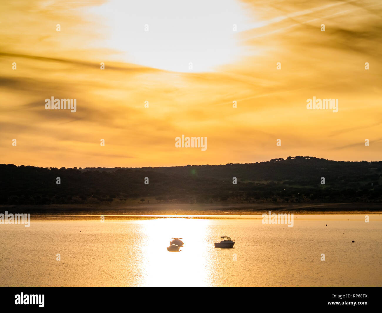 Boats on a lake at sunset, moored with a buoy and calm water in the reservoir of La Maya (Salamanca) - Stock Image