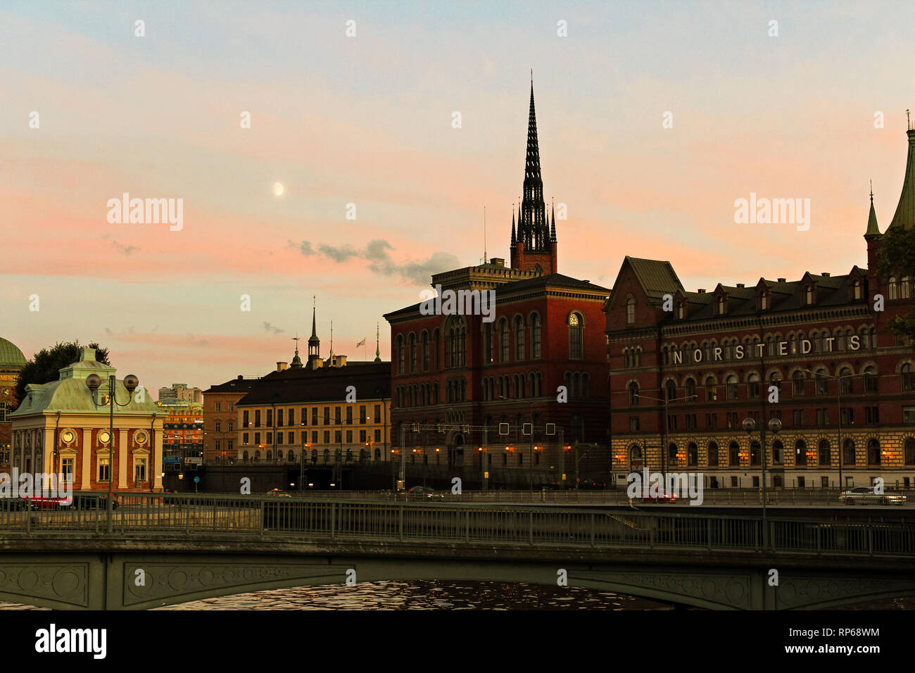 Moon rising over Gamla Stan and behind Riddarholmskyrkan in front of red sunset sky during summer (Stockholm, Sweden, Europe) - Stock Image
