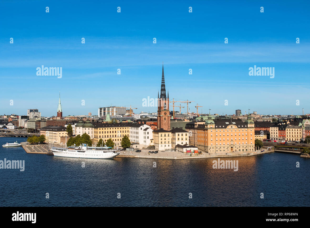 View onto Gamla Stan with Riddarholmskyrkan and a white large ship as seen from Södermalm during summer (Stockholm, Sweden, Europe) - Stock Image
