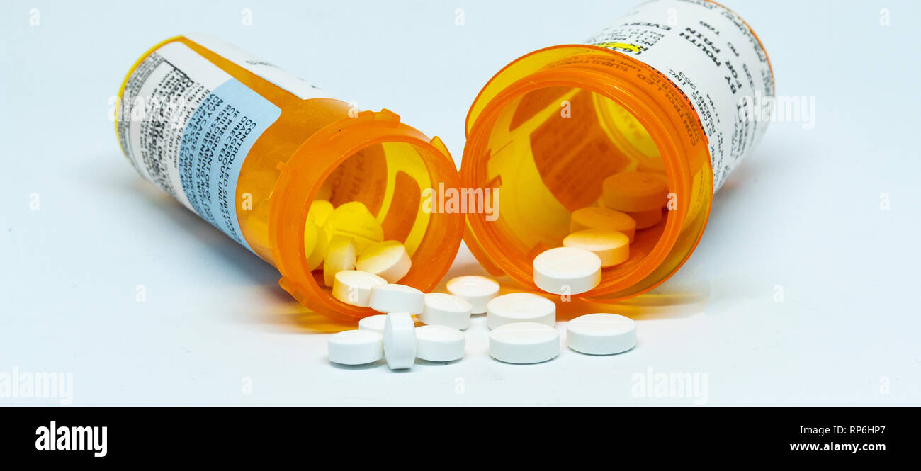Two prescription bottles with pain pills spilling out of them with a white background. Stock Photo