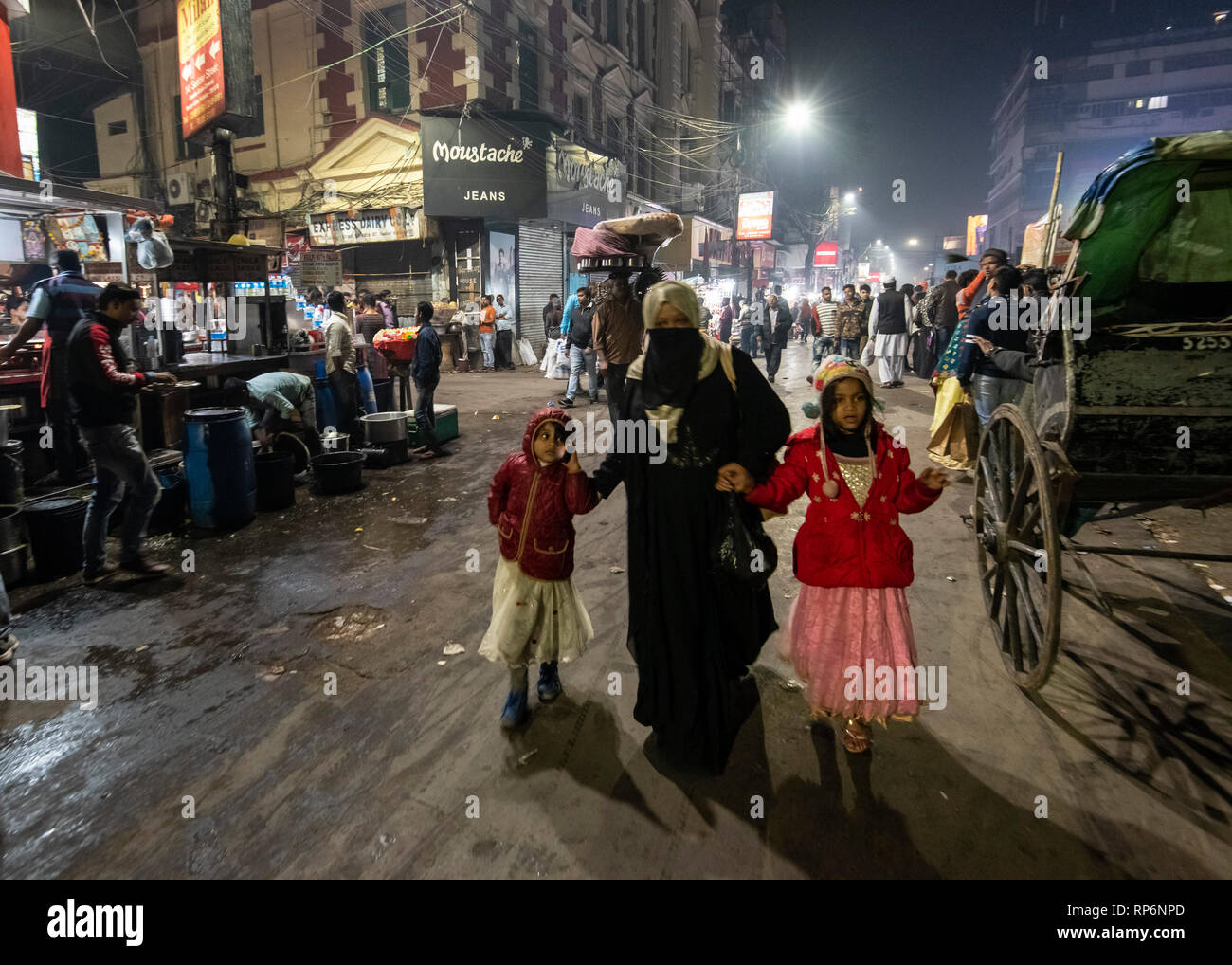 Typical atmospheric busy noisy night time street scene in Kolkata with local people, rickshaws and street food vendors. - Stock Image
