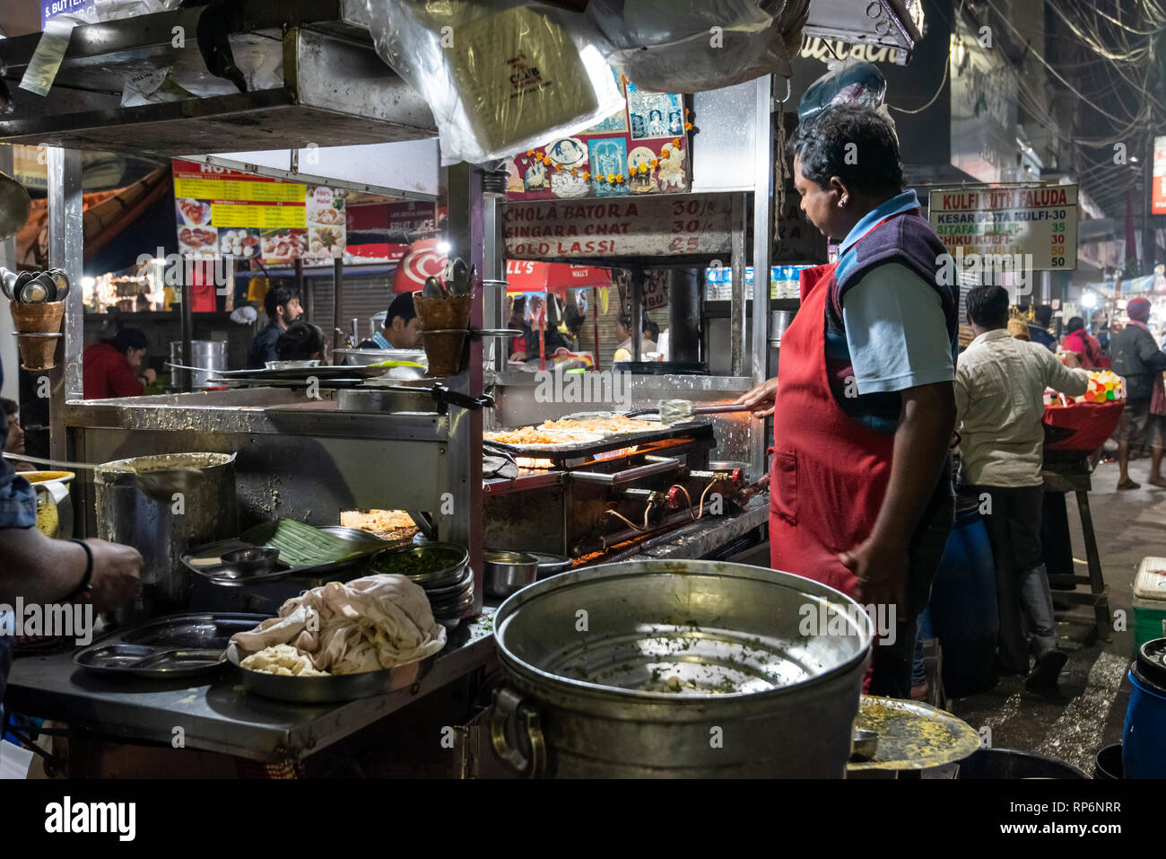 Typical atmospheric busy noisy night time street scene in Kolkata with a street food vendor making Mughlai paratha a popular Bengali street food. - Stock Image