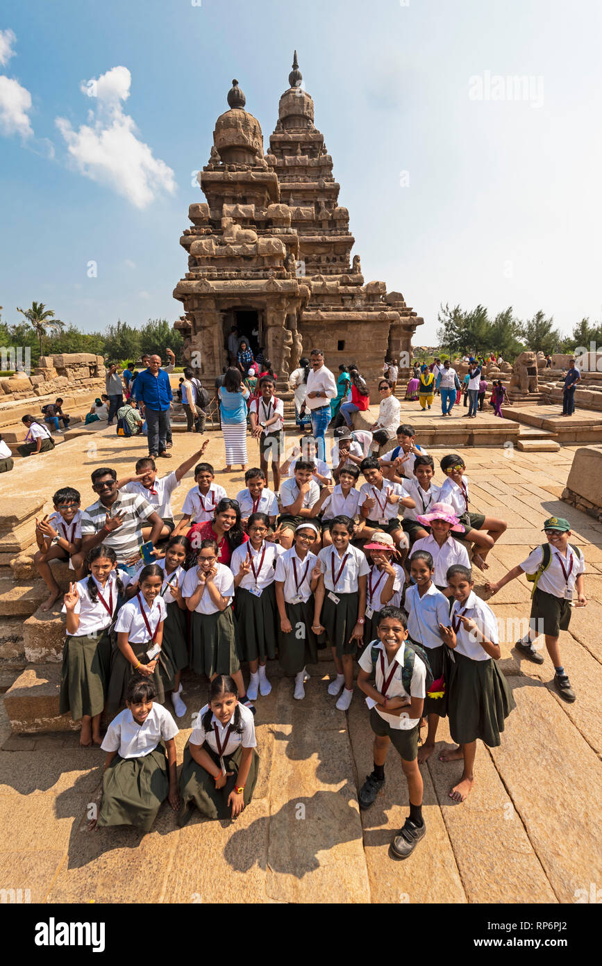 A group of local Indian school children pose for the camera in front of The Shore Temple in Mahabalipuram with tourists and locals visiting. - Stock Image