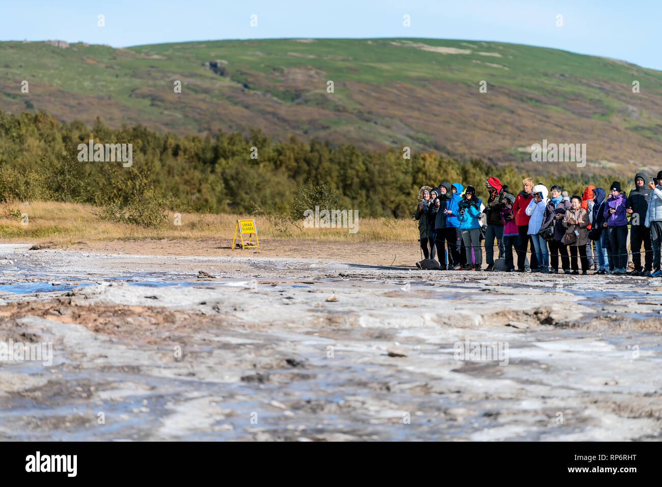 Haukadalur Valley, Iceland - September 19, 2018: Geyser landscape with people group waiting in south Icelandic country by Strokkur Geysir Hot Springs  Stock Photo