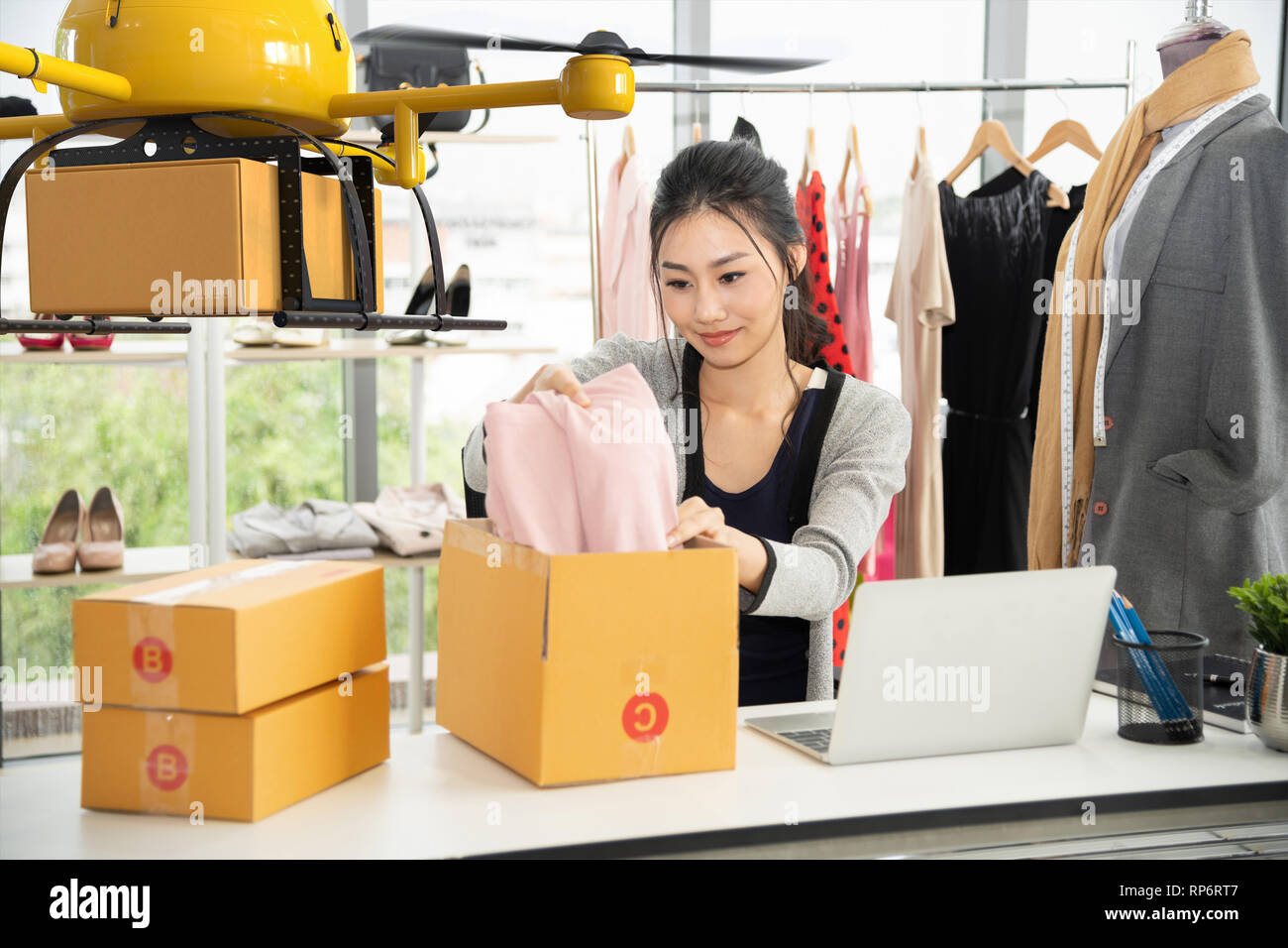 Young asian women packing cloth on box for delivery to customer by air drone, Small business with modern technology shipment innovation and eco concept Stock Photo