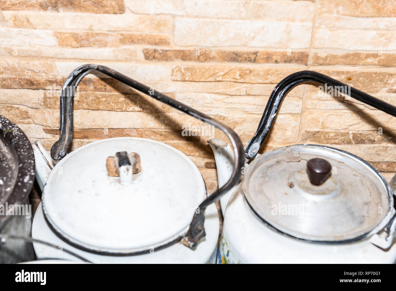 Closeup of many large pots and pans kettle teapots lids on rustic dacha country home or house cottage kitchen stove with dirt - Stock Image