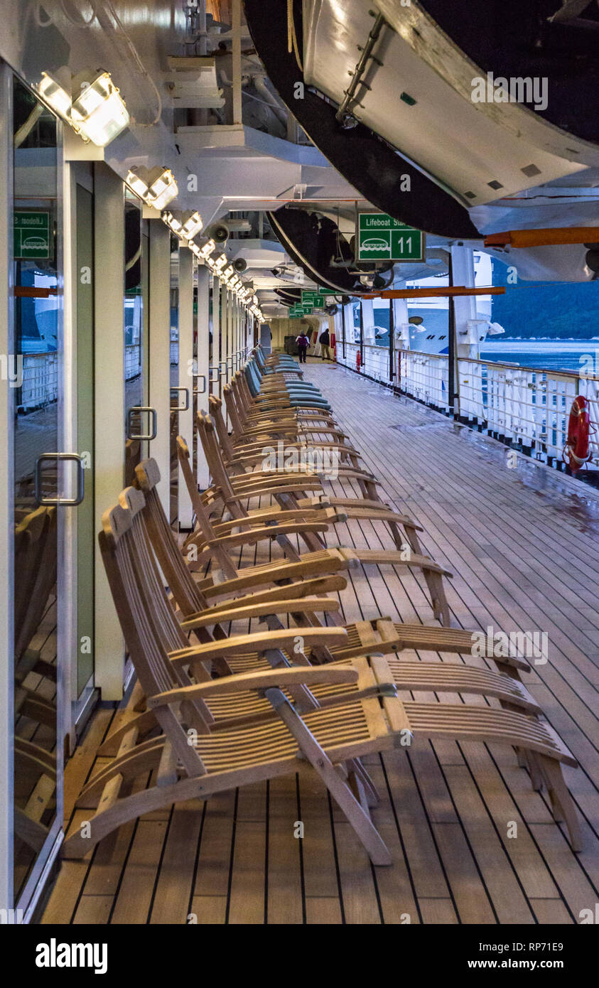 September 15, 2018 - Skagway, AK: Row of cruise ship empty wooden outdoor deck chairs aboard Holland America's The Volendam. Very early morning, while - Stock Image