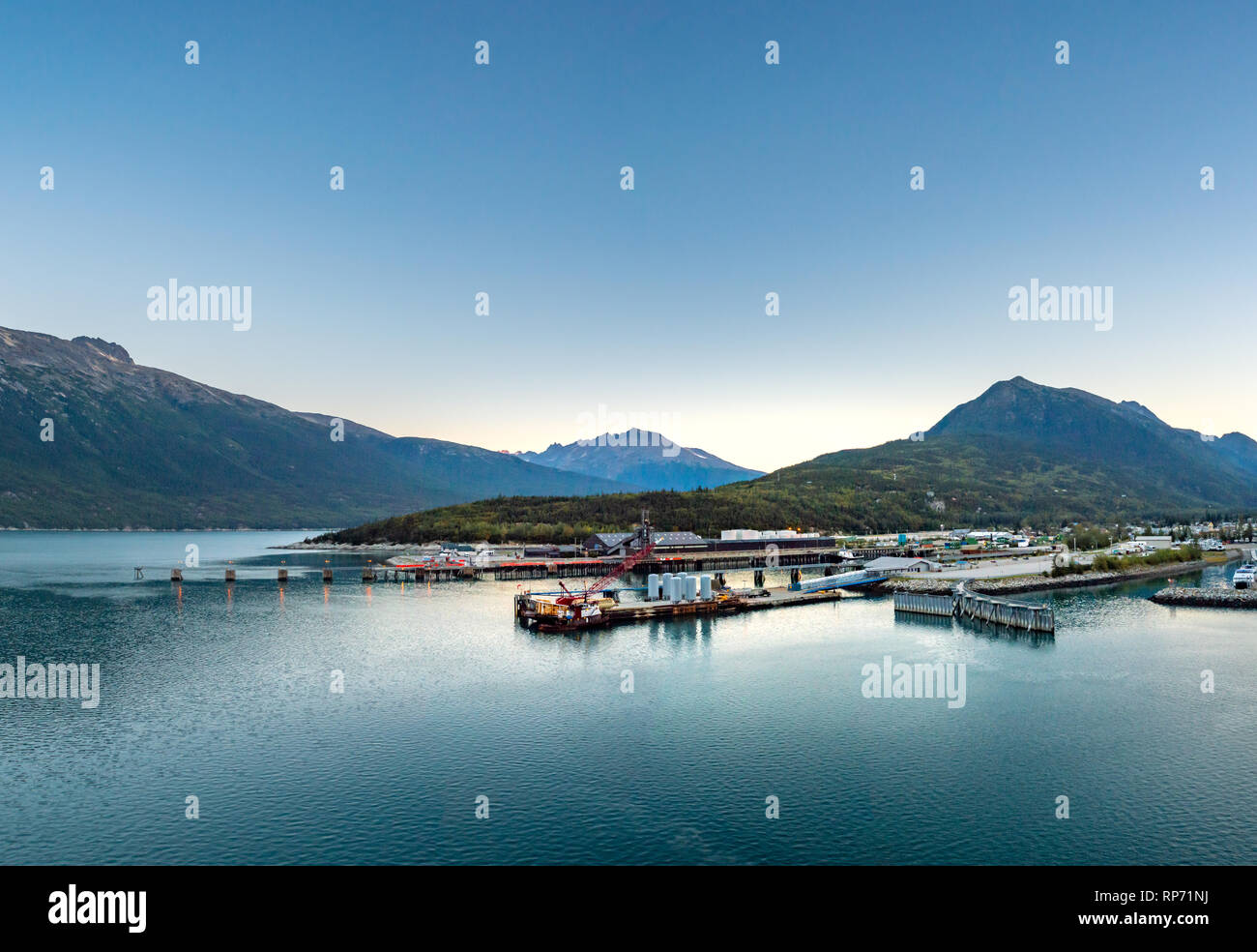 September 15, 2018 - Skagway, AK: Small boat harbour and industrial docks at sunrise, looking Northwest from cruise ship terminal in port. - Stock Image