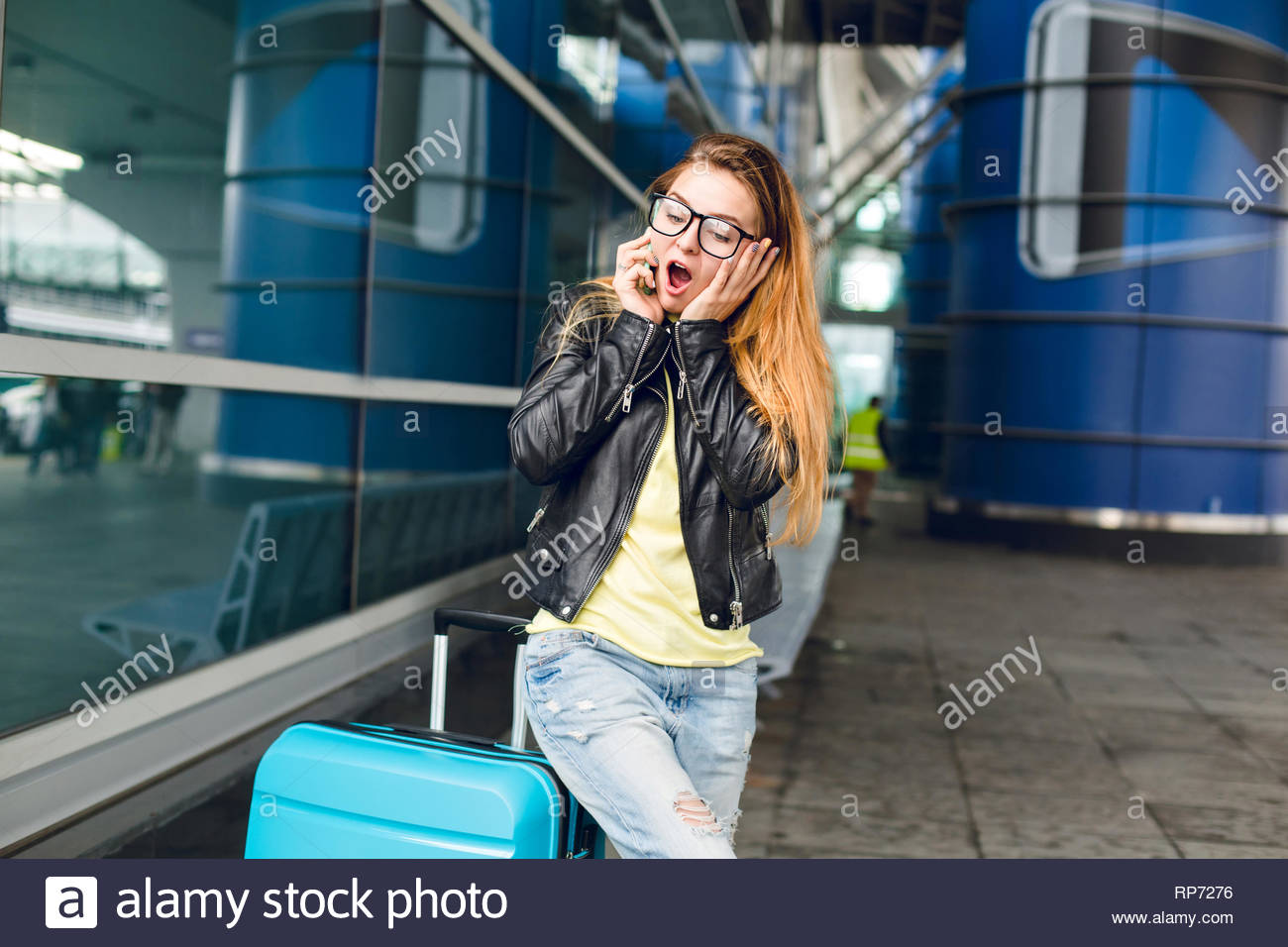 Young girl with long hair in black jacket is standing near suitcase outside in airport. She has long hair, black glasses. Speaking on phone intrigued. - Stock Image
