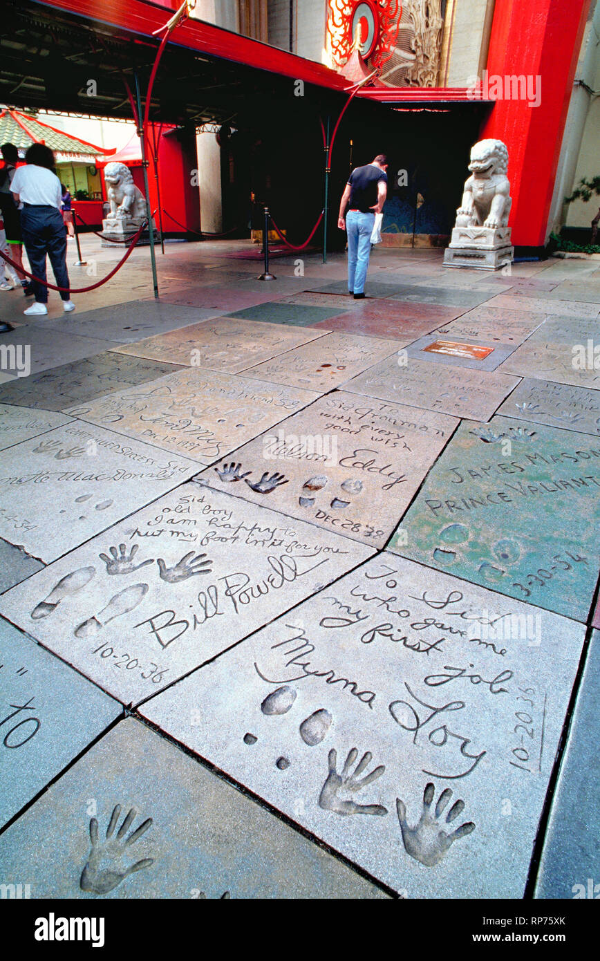 The handprints, footprints and autographs of famous celebrities have be cast in concrete in the Forecourt of the Stars since 1927 at the Chinese Theatre in Hollywood, California, USA.  Long known as Grauman's Chinese Theatre, it was later called Mann's Chinese Theatre and is now named the TLC Chinese Theatre. Impressions in the foreground were made in 1936 by two movie stars who appeared in 14 films together, William Powell and Myrna Loy. They are among early signees who inscribed personal messages to Sid Grauman, the man who built the lavish movie house and managed it until his death in 1950. - Stock Image