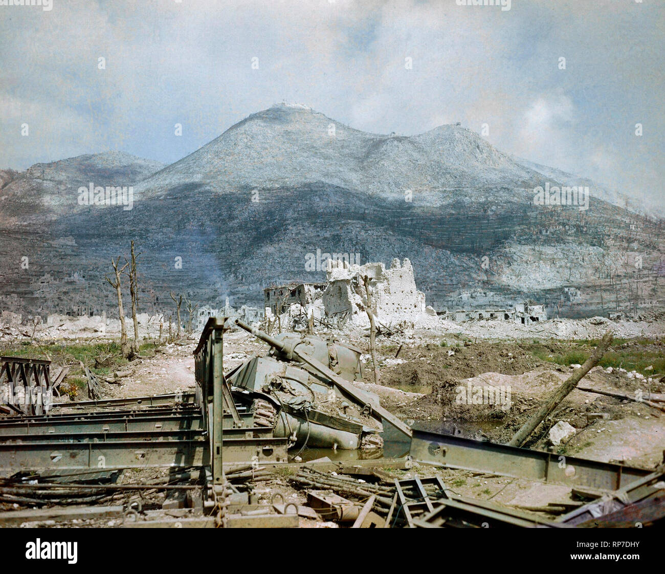 The ruins of Cassino, May 1944: a wrecked Sherman tank and Bailey bridge in the foreground, with Monastery Ridge and Castle Hill in the background. View of Cassino after heavy bombardment showing a knocked out Sherman tank by a Bailey bridge in the foreground with Monastery Ridge and Castle Hill in the background. - Stock Image