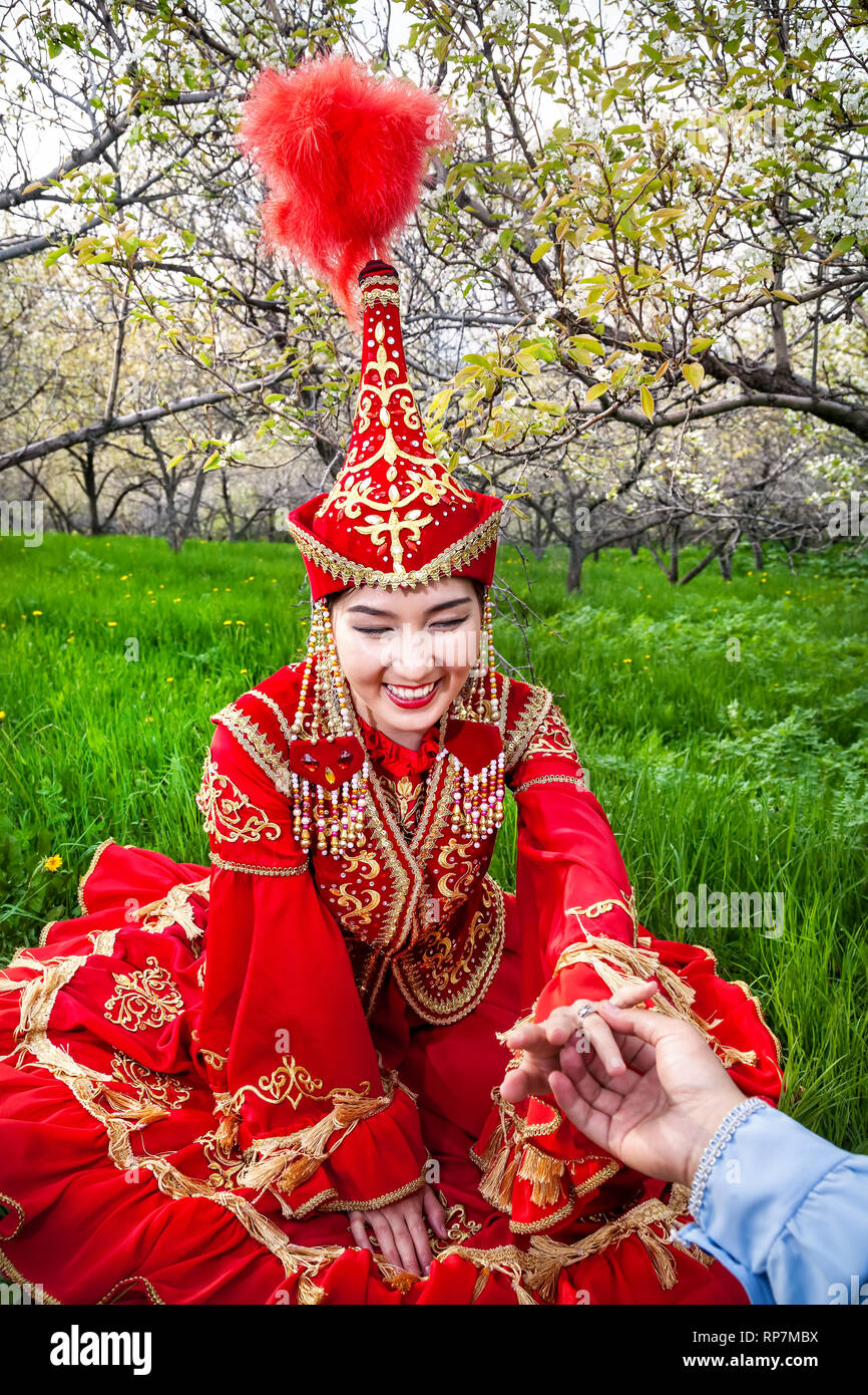 Happy woman in Kazakh red costume with wedding ring present of her boyfriend at spring garden in Kazakhstan. Proposal concept. - Stock Image