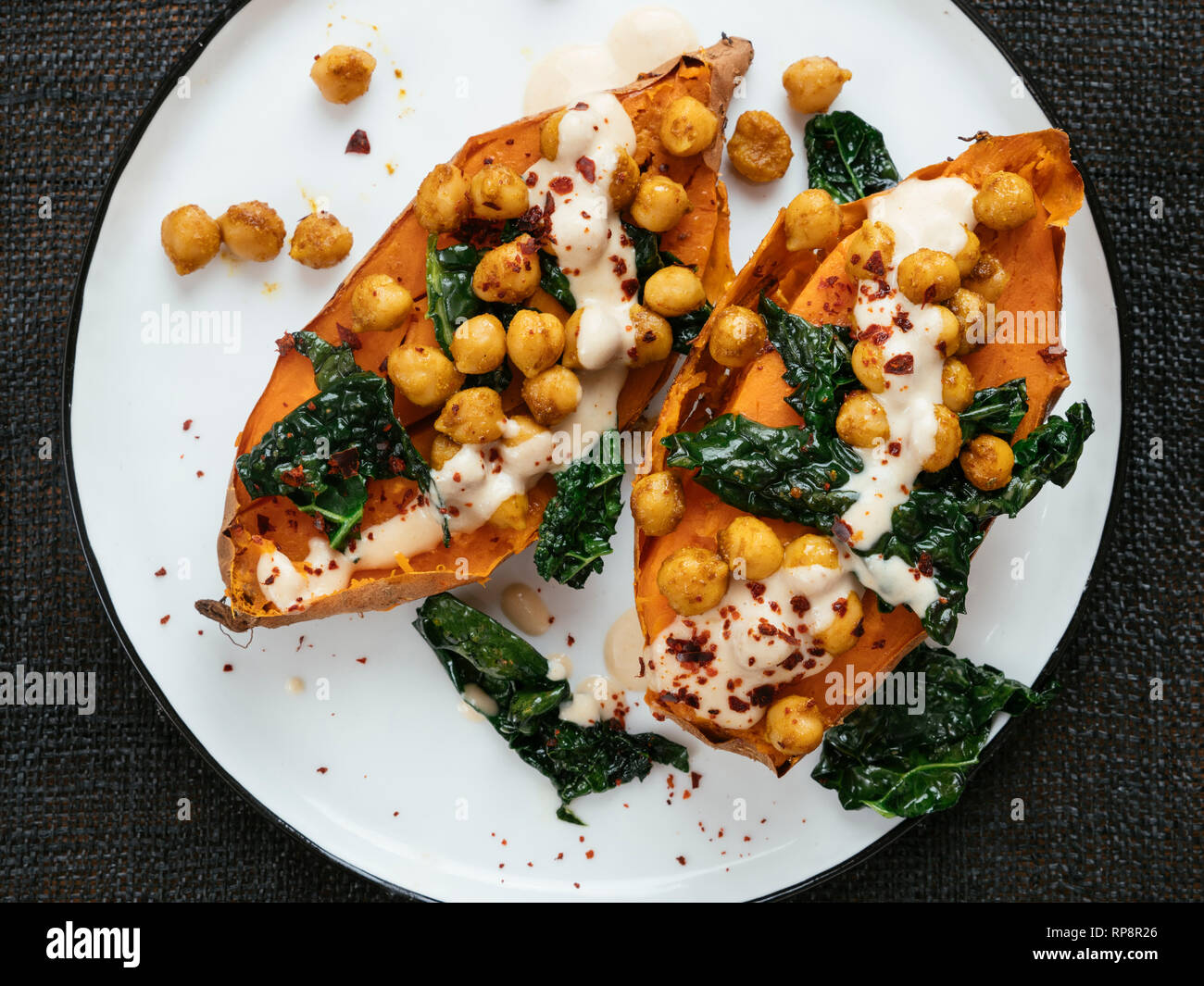 Baked sweet potatoes loaded with spicy chickpeas and kale and a tahini Dressing. - Stock Image