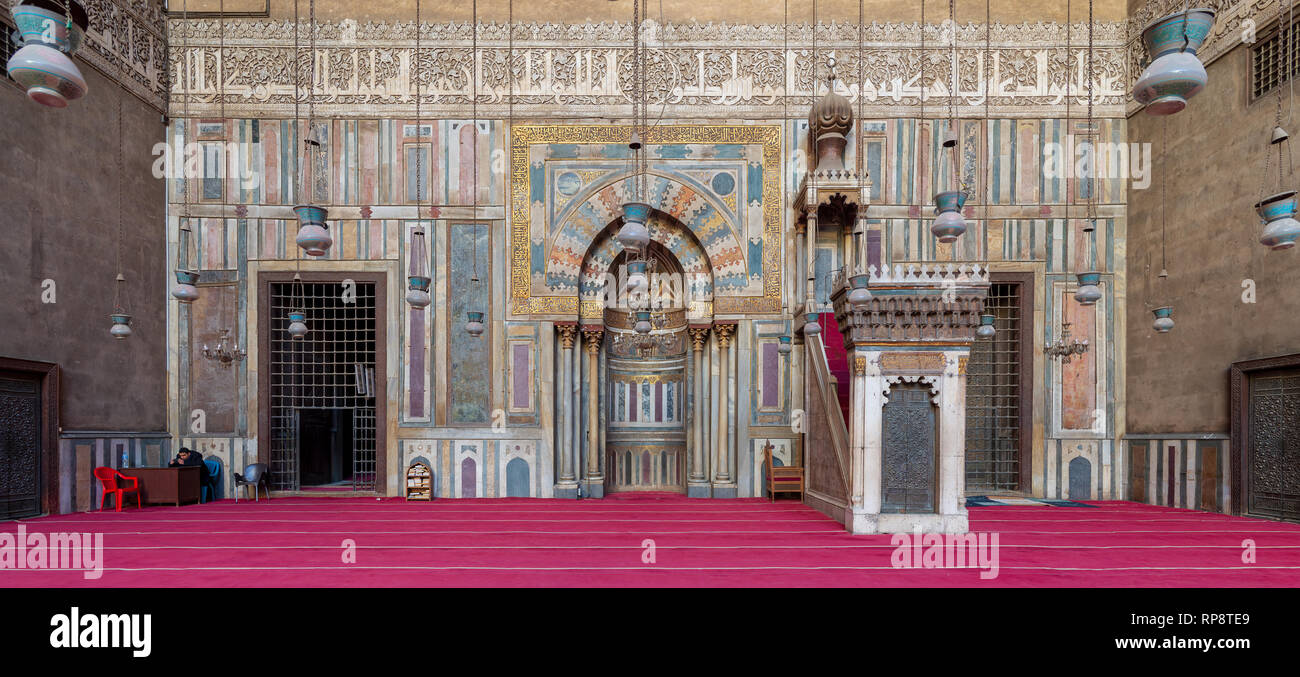 Cairo, Egypt - January 8 2019: Colorful decorated marble wall with engraved Mihrab (niche) and wooden Minbar (Platform) at the Mosque and Madrassa (Sc - Stock Image