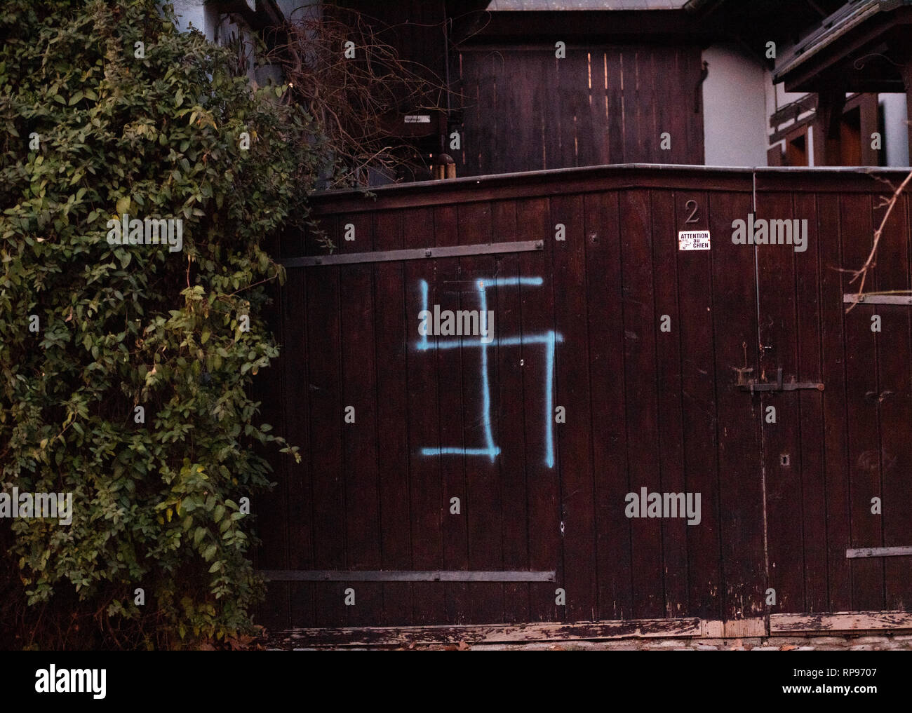 Vandalised with nazi swastika symbols in blue spray-painted on the entrance door of a house near Jewish cemetery in Quatzenheim near Strasbourg  - Stock Image