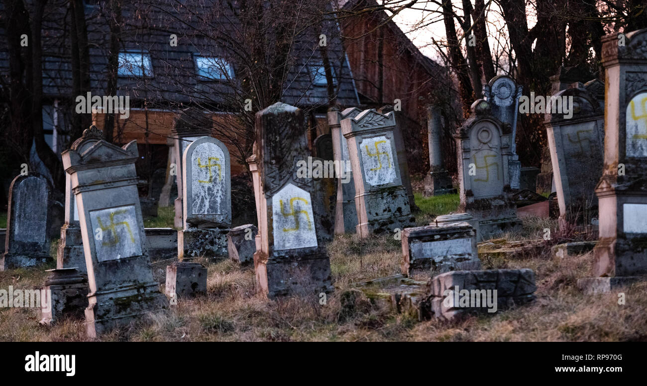 Vandalised graves with nazi symbols in blue spray-painted on the damaged graves - Jewish cemetery in Quatzenheim near Strasbourg  - Stock Image