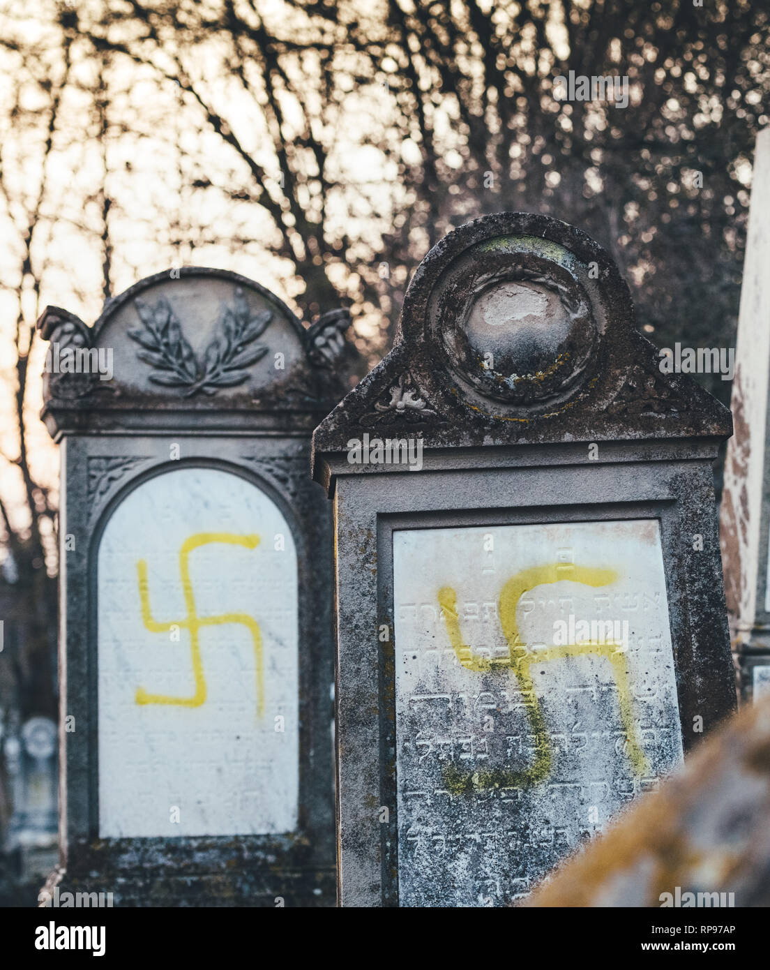 Vertical image of vandalised graves with nazi symbols in