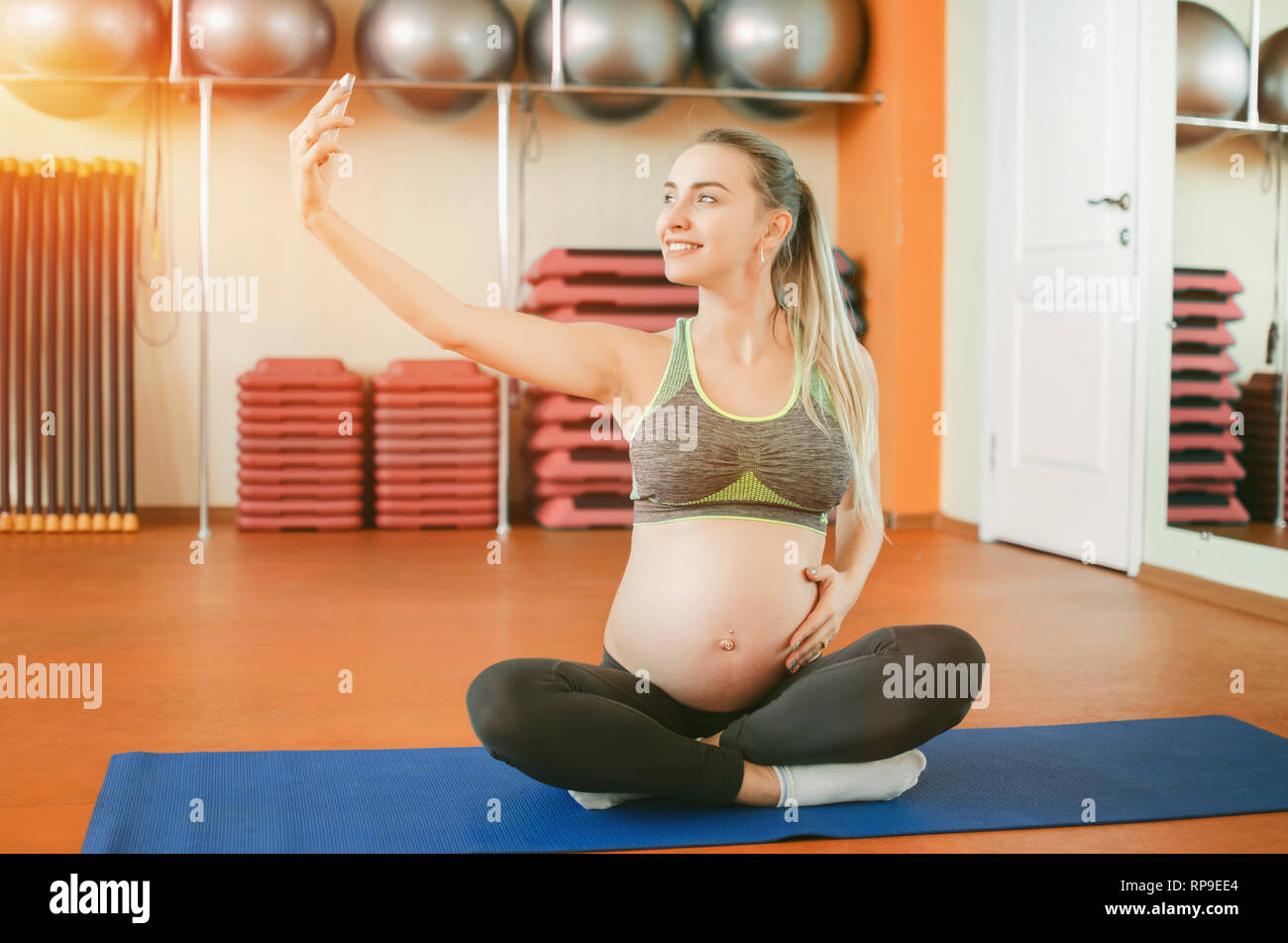 Yoga for pregnant women. Young beautiful pregnant girl sitting in the lotus position and making selfie - Stock Image